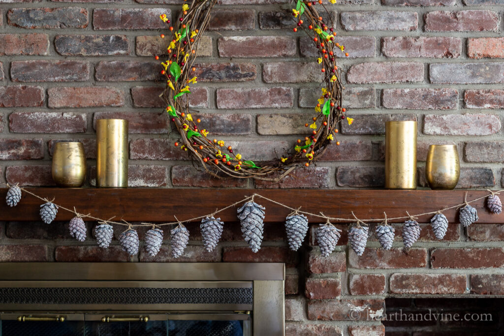 Faux bleached pinecone garland hung on a mantel with gold vases and a grapevine wreath.
