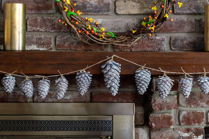 Fall mantel with whitewashed pinecone garland.
