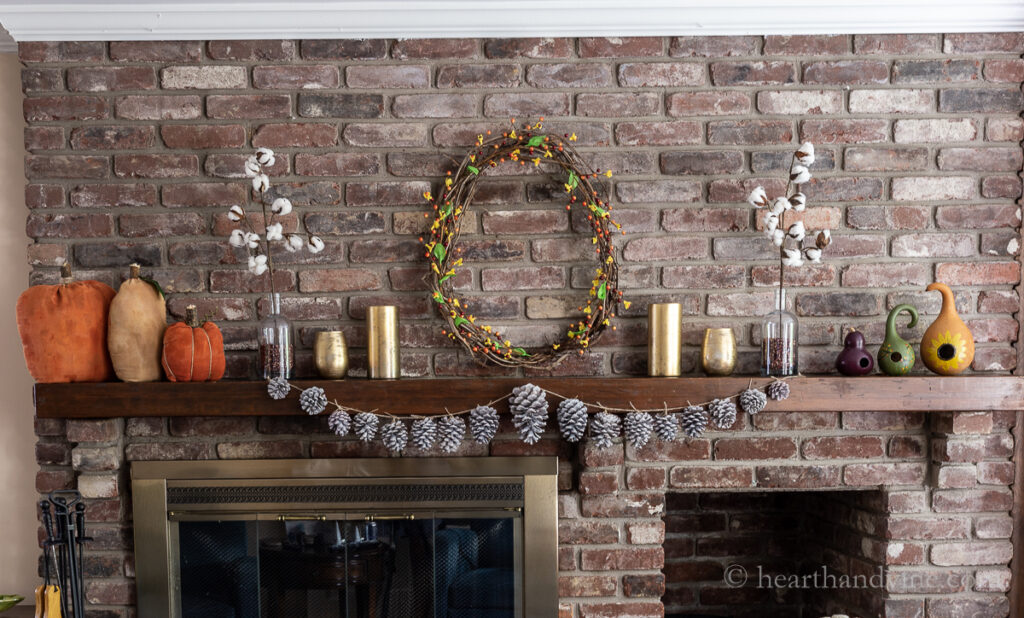 Simple fall mantel ideas full view of pumpkins, gourds, pinecone garland, bittersweet wreath and gold vases.