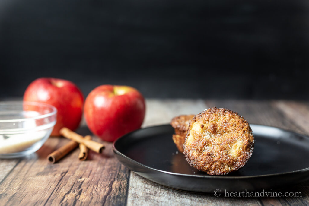 Apple oat muffins on a plate next to some apples and cinnamon sticks.