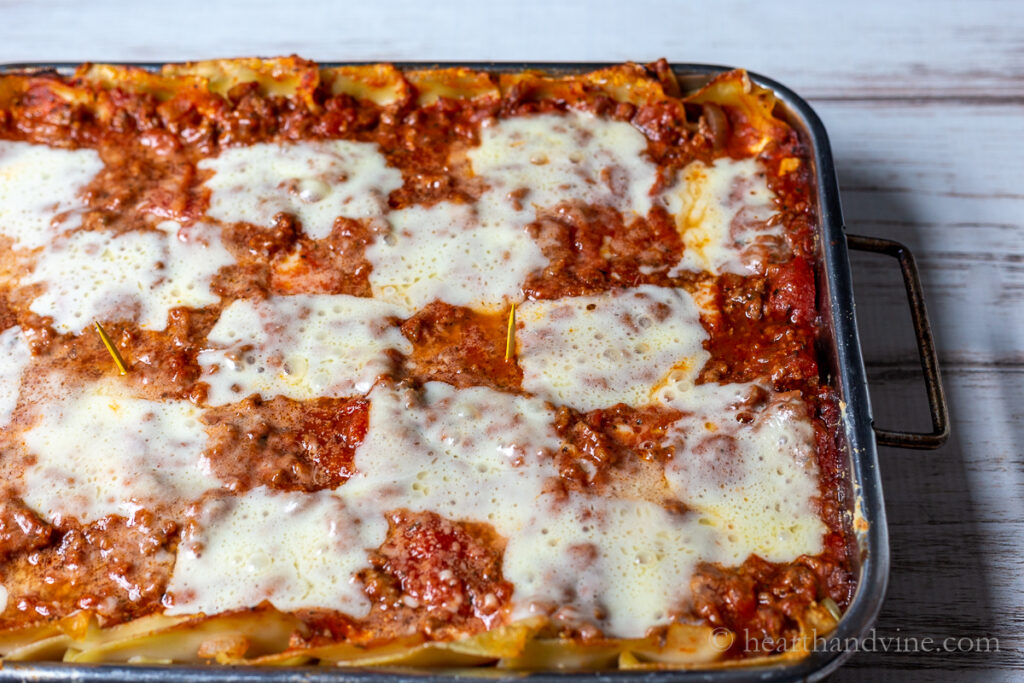 Italian lasagna with toothpicks spaced evenly throughout.