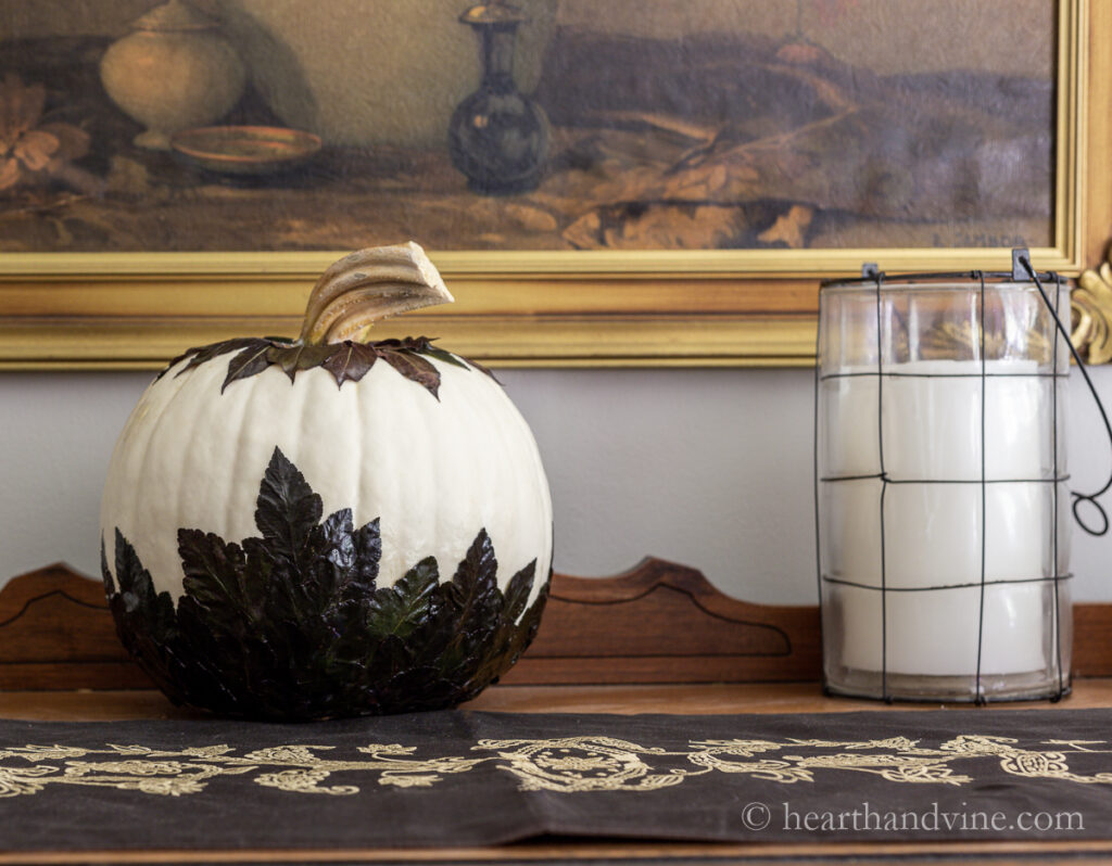 White pumpkin decorated with leaves on a buffet next to a candle.
