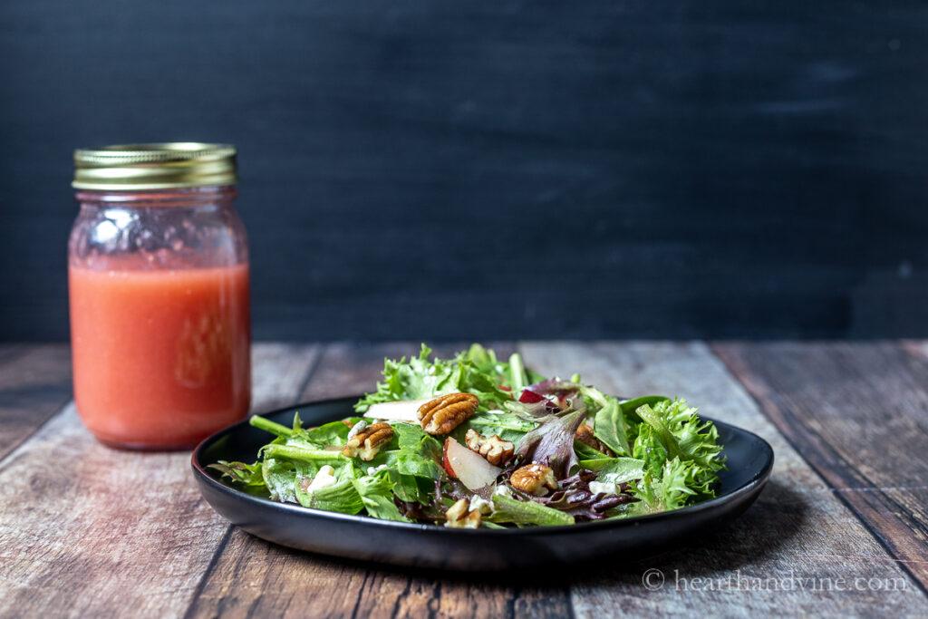 Pear gorgonzola salad with plum vinaigrette mason jar on the side.