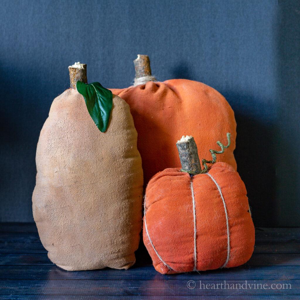 Three primitive fabric pumpkins on a table.