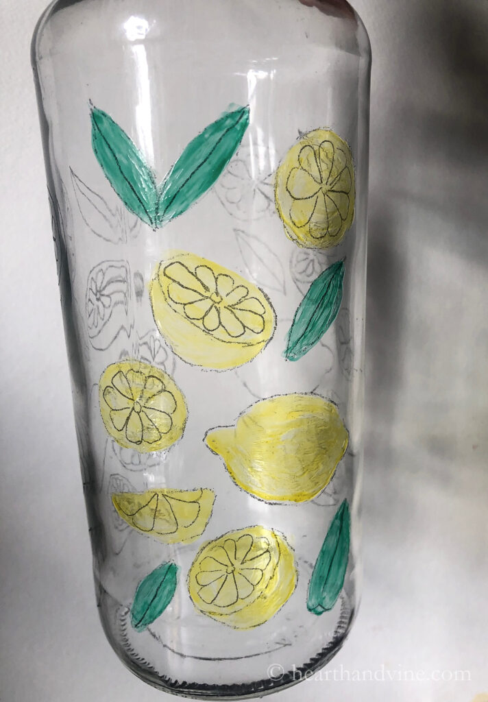 Lemons and leaves bottle art painting on a clear wine bottle.