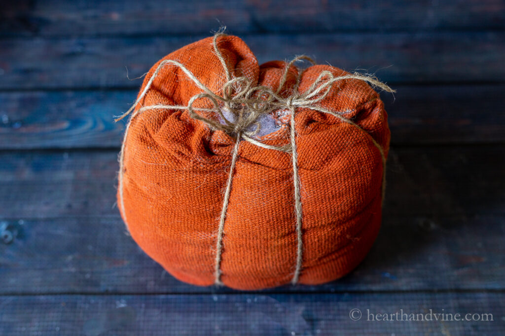 Small primitive fabric pumpkin with twine tied at the top and pulled tightly to create ribbing.