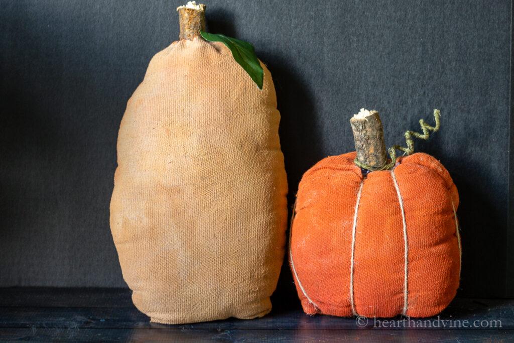 Tall squash stuffed pumpkin and short twine ribbed pumpkin on table.