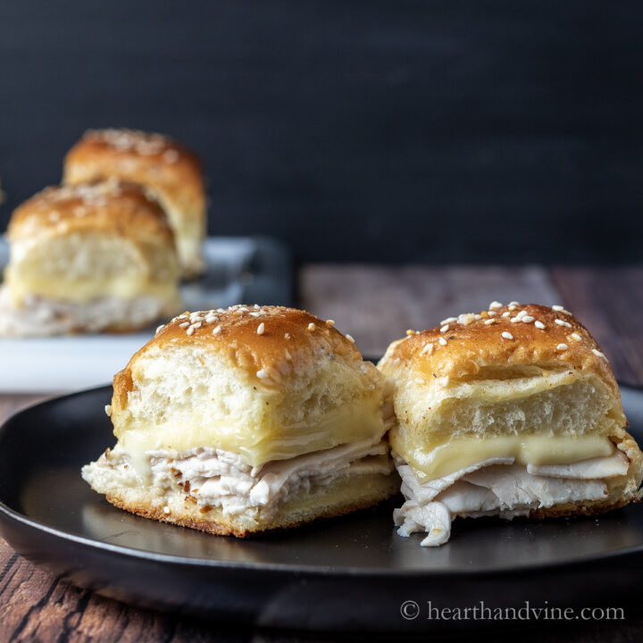 Two turkey ranch sliders with gouda cheese on a plate.