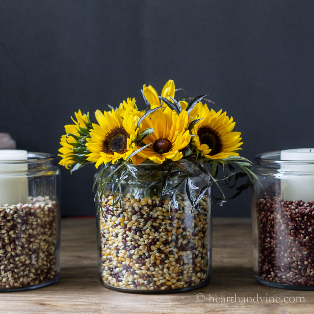 Apothecary jars with sunflowers, candles and colored popcorn kernels.