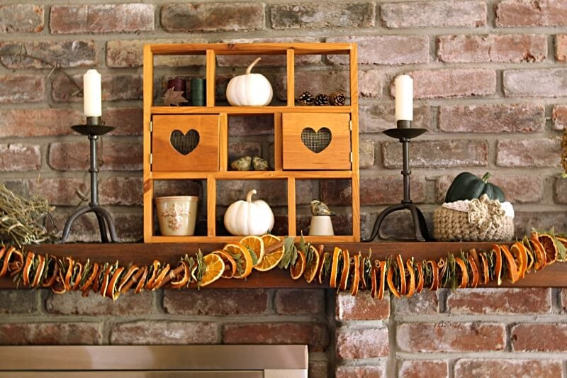 Close up of fall mantel with pumpkins orange garland and candle sticks