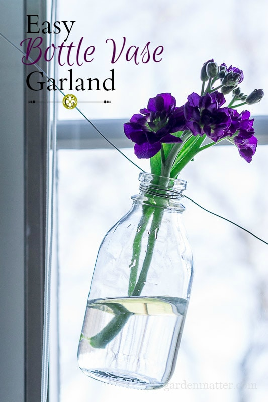 Hanging bottle flower garland with purple stock.