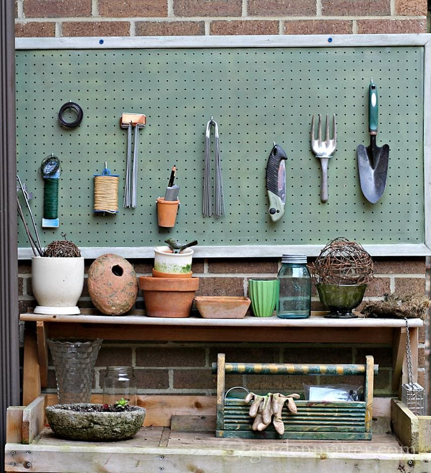 Organizer pegboard for garden supplies above potting bench